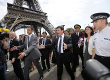 French Interior Minister Valls gestures as he walks with Junior Minister of Crafts, Business and Tourism Pinel surrounded by journalists next to the Eiffel Tower in Paris